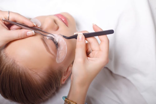 Eyelash Extension Procedure. Woman Eye with Long Eyelashes. Lashes. Close up, selected focus.